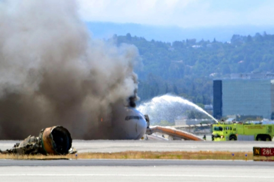 Firefighters spray water on Asiana Airlines flight 214 as it sits on the runway burning at San Francisco Airport International Airport