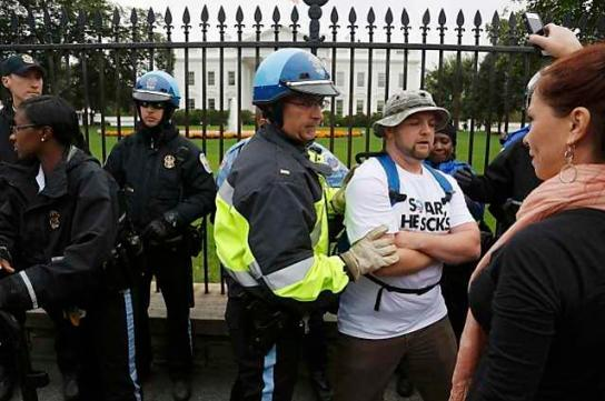 Law enforcement officers force protesters down from the fence in front of the White House gates in Washington
